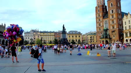 kamienice : KRAKOW, POLAND - JUNE 10, 2018: Crowded Main Market Square or Plac Mariacki with monument to Adam Mickiewicz, bell towers of St Marys Basilica, old townhouses, cafes and stalls, on June 10 in Krakow.