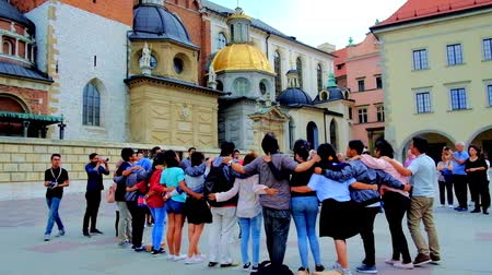 wawel : KRAKOW, POLAND - JUNE 10, 2018: The group of tourists, hugging in circle, sing religious songs in courtyard of Wawel Castle next to the Chapels of Cathedral, on June 10 in Krakow.