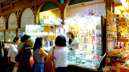 sukiennice : KRAKOW, POLAND - JUNE 10, 2018: Female tourists choose silver and amber jewelries in shop of Cloth Hall (Sukiennice) - the handicraft market on the Main Square (Plac Mariacki), on June 10 in Krakow. Stock Footage