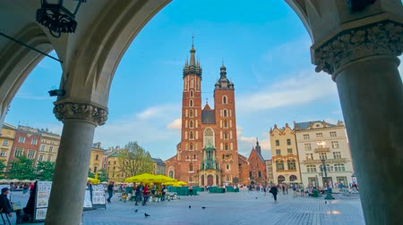 kamienice : KRAKOW, POLAND - JUNE 12, 2018: The Gothic bell towers of St Marys Basilica are seen through the arcade of Cloth Hall (Sukiennice), located on Mariacki or Main Market Square, on June 12 in Krakow.