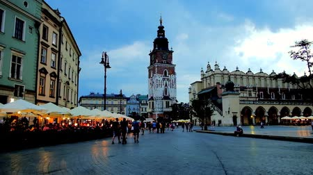 sukiennice : KRAKOW, POLAND - JUNE 10, 2018: The evening on Main Market Square with a view on Town Hall Tower, Cloth Hall, summer restaurants, outdoor cafes and bars, on June 10 in Krakow. Stock Footage