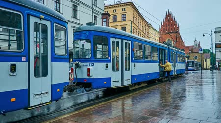 kamienice : KRAKOW, POLAND - JUNE 13, 2018: The trams ride along the All Saints Square with a view on Holy Trinity Basilica on wet rainy weather, on June 13 in Krakow.