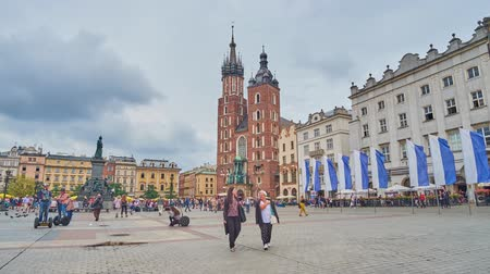 kamienice : KRAKOW, POLAND - JUNE 13, 2018: Market (Mariacki, Main) Square boasts many historical landmarks - Adam Mickiewicz monument, St Marys Basilica, medieval mansions and Cloth Hall, on June 13 in Krakow. Stock Footage