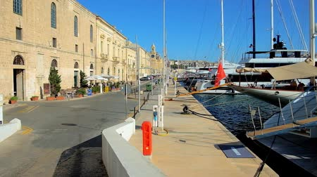 lâmina : BIRGU, MALTA - JUNE 17, 2018: Xatt Il-Forn seaside promenade stretches along the medieval edifices and marina of Vittoriosa (Birgu) with sail yachts and boats, on June 17 in Birgu.