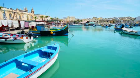 takımadalar : MARSAXLOKK, MALTA - JUNE 18, 2018: The harbour of fishing village with traditional luzzu boats among the ordinary vessels, cozy cafes and tourist stalls along the shore, on June 18 in Marsaxlokk Stok Video