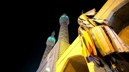 yazd : The minarets of Shahzade Fazl Holy Shrine with the night sky and waving pieces of colored cloth, Yazd, Iran.