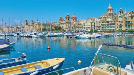 мальтийский : SENGLEA, MALTA - JUNE 19, 2018: The rows of white yachts in marina of Vittoriosa with the mansions and churches of Birgu on background, on June 19 in Senglea. Стоковые видеозаписи