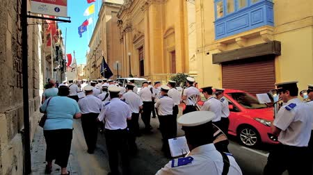 festa : BIRGU, MALTA - JUNE 17, 2018: The brass band marches along the medieval edifices in narrow street of Vittoriosa (Birgu) during the city festival, on June 17 in Birgu.