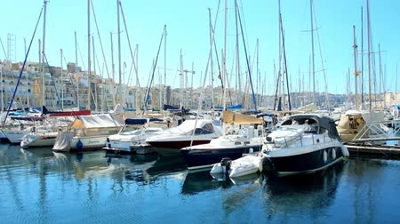 maltština : BIRGU, MALTA - JUNE 17, 2018: The walk along the seaside promenade with a view on yachts in marina of Vittoriosa and the medieval edifices of Senglea (L-Isla) behind the harbour, on June 17 in Birgu.