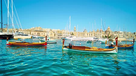 maltština : SENGLEA, MALTA - JUNE 19, 2018: Traditional Malteze dghajsa water taxies are bobbing on the waves in harbor with a view on medieval buildings of Birgu (Vittoriosa) on background, on June 19 in Senglea