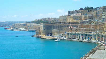 мальтийский : The fortress walls of Valletta opens the perfect view on Quarry Wharf with medieval buildings, ramparts, bastions and boats in harbour, Valletta, Malta.
