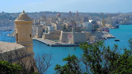 Мальта : Medieval fortified city of Senglea (L-Isla), surrounded by blue waters of Grand Harbour (Port of Valletta) with small tower of Valletta fortress on the foreground, Malta. Стоковые видеозаписи