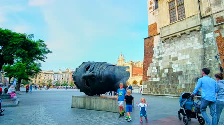 sukiennice : KRAKOW, POLAND - JUNE 12, 2018: The modern sculpture, named Eros Bendato (Eros Bound) attracts the tourists and children, located at the Town Hall Tower in Main Square, on June 12 in Krakow. Stock Footage