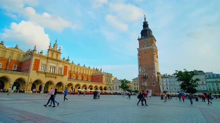 kamienice : KRAKOW, POLAND - JUNE 12, 2018: The medieval Town Hall Tower and Cloth Hall (Sukiennice) - the central handicraft market, located on the crowded Main Square or Plac Mariacki, on June 12 in Krakow. Stock Footage