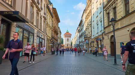 kamienice : KRAKOW, POLAND - JUNE 11, 2018: Florianska street is popular shopping and walking area with numerous cafes, bars, stores and medieval St Florians Gate on background, on June 11 in Krakow.