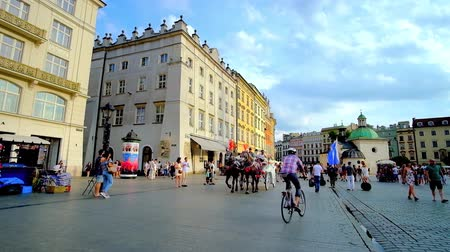 kamienice : KRAKOW, POLAND - JUNE 10, 2018: The horse-drown carriages ride in Plac Mariacki (Main or Market Square) with a view on St Adalbert Church and old townhouses on the background, on June 10 in Krakow.