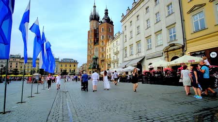 kamienice : KRAKOW, POLAND - JUNE 10, 2018: The Main Square (Plac Mariacki) with many cozy cafes and restaurants, attracting tourists, walking in Old Town (Stare Miasto), on June 10 in Krakow.