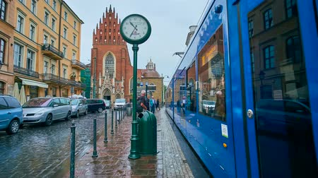 kamienice : KRAKOW, POLAND - JUNE 13, 2018: The  All Saints Square with a view on trams, that stop on the station, people under umbrellas and Holy Trinity Basilica on a rainy day, on June 13 in Krakow.
