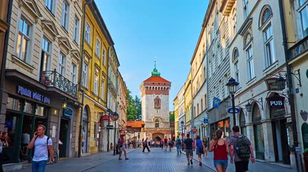 kamienice : KRAKOW, POLAND - JUNE 11, 2018: The walk along theshopping Florianska street with its cafes and souvenir stores to historical St Florians Gate - the part of preserved rampart, on June 11 in Krakow.