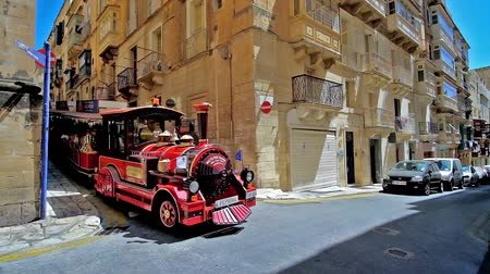 Мальта : VALLETTA, MALTA - JUNE 17, 2018: The Malta Fun Train entertain the tourists, riding in narrow city streets among historical mansions, small cafes and old churches, on June 17 in Valletta Стоковые видеозаписи