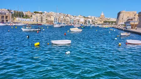 haven : BIRGU, MALTA - JUNE 17, 2018: Il-Marina of Kalkara with medieval architecture along the shores, rampart of Birgu, small fishing boats, yachts and St Josephs Church on background, on June 17 in Birgu. Stock Footage