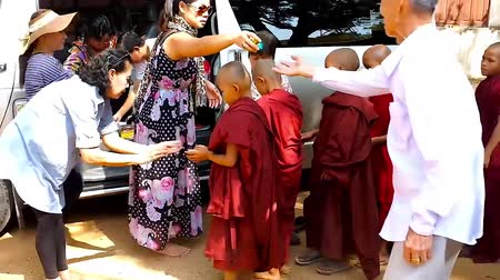pagan kingdom : BAGAN, MYANMAR - FEBRUARY 25, 2018: The pilgrims give sweets to the orphans - novice monks (samaneras) of Shwe Gu Buddhist Training Monastery, on February 25 in Bagan. Stock Footage