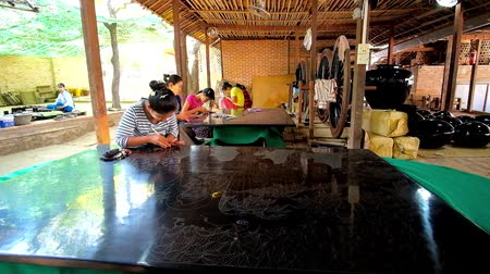 lacquerware : BAGAN, MYANMAR - FEBRUARY 25, 2018: The artisan creates the picture on the lacquer panel, using etching needle, sitting on the floor in open air terrace of the workshop, on February 25 in Bagan.