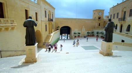 papież : VICTORIA, MALTA - JUNE 15, 2018: Cathedral Square in Cittadella (Il Castello) of Rabat with statues of Popes Pius IX and John Paul II, huge rampart and medieval edifices, on June 15 in Victoria.