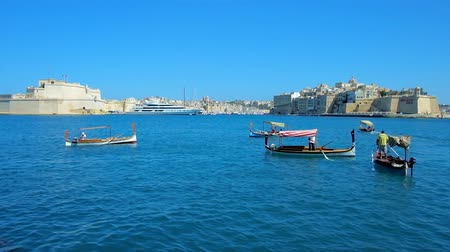 bastião : VALLETTA, MALTA - JUNE 17, 2018: The dghajsa and luzzu traditional Maltese boats at Quarry Wharf with a view on fortified cities of Birgu and Senglea, on June 17 in Valletta.