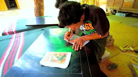 kružba : BAGAN, MYANMAR - FEBRUARY 25, 2018: The artisan of the local lacquerware workshop scratches the lacquer panel with etching needle to create a picture, on February 25 in Bagan.