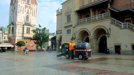 kamienice : KRAKOW, POLAND - JUNE 11, 2018: The street sweeper vehicle washes area at the entrance to the Cloth Hall in Main Square, using water spray and brushes, on June 11 in Krakow.