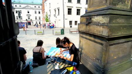 panské sídlo : KRAKOW, POLAND - JUNE 11, 2018: The students of Art Academy create the sketches and paintings of architectural forms, sitting in shade of the stone fence in Godzka street, on June 11 in Krakow. Dostupné videozáznamy