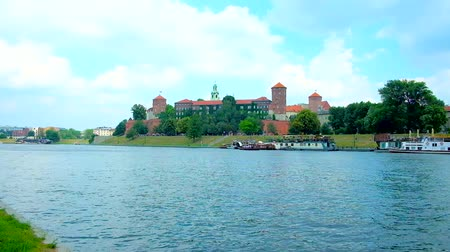 wawel : The joyful walk along the bank of Vistula river with a view on picturesque Wawel Fortress, surrounded by green garden, Krakow, Poland.