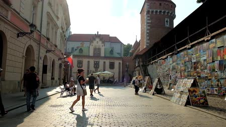 kamienice : KRAKOW, POLAND - JUNE 11, 2018: The  historical mansions, medieval rampart and tower of St Florian Gate (Brama Florianska) and art vernissage, stretching along Pijarska street, on June 11 in Krakow.