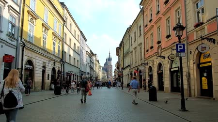 kamienice : KRAKOW, POLAND - JUNE 11, 2018: The Florianska street with historical edifices, stretching to the Main Square with a view on tall bell towers of St Mary Basilica, on June 11 in Krakow.