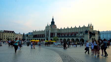 sukiennice : KRAKOW, POLAND - JUNE 11, 2018: The crowded Main Square with a view on scenic building of Cloth Hall (Sukiennice) - the main handicraft market in city, on June 11 in Krakow.