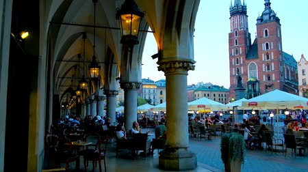 sukiennice : KRAKOW, POLAND - JUNE 11, 2018: The view from the arcade of the Cloth Hall (Sukiennice) on crowded outdoor cafes and Gothic St Marys Basilica in Market (Mariacki, Main) Square, on June 11 in Krakow.