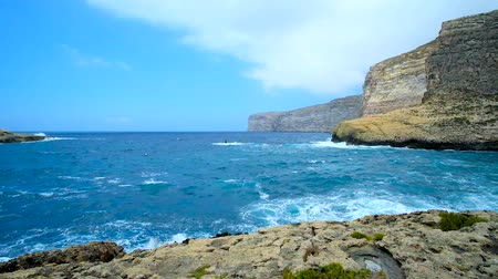 maltština : The lazy walk along the coast of Xlendi tourist village with a view on tall rocky cliffs, lumpy sea waters and fast moving clouds, Gozo Island, Malta.