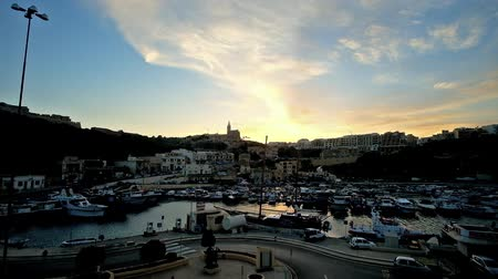 ferry terminal : GHAJNSIELEM, MALTA - JUNE 15, 2018: The scenic fishing harbor with boats, rocky hills and tall silhouette of Parish Church on twilight, on June 15 in Ghajnsielem.