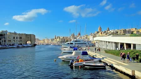 lâmina : BIRGU, MALTA - JUNE 17, 2018: The view from Bormla (Cospicua) bridge on motor boats, ferry terminal and old cities of Birgu and Senglea on shores of Vittoriosa Marina, on June 17 in Birgu Stock Footage