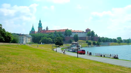 wawel : KRAKOW, POLAND - JUNE 11, 2018: The green lawn on the gentle hill along Vistula river is the perfect place for picnics with a view on medieval Wawel Castle, surrounded by garden, on June 11 in Krakow. Stock Footage