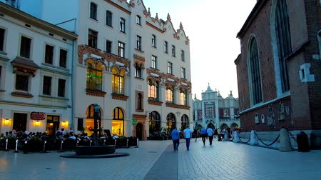 kamienice : KRAKOW, POLAND - JUNE 11, 2018: The evening Mariacki Square with old townhouses, outdoor terraces of restaurants, small fountain in the middle and Cloth Hall on the distance, on June 11 in Krakow Stock Footage