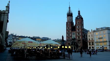 kamienice : KRAKOW, POLAND - JUNE 11, 2018: The crowded outdoor cafe with a view on St Mary Basilica in the evening Market Square, on June 11 in Krakow.