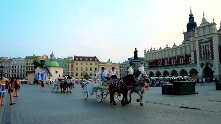 sukiennice : KRAKOW, POLAND - JUNE 11, 2018: The evening Market Square with crowds of tourists, riding horse-drawn carriages, medieval building of Cloth Hall and St Adalbert Church, on June 11 in Krakow.
