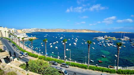 мальтийский : Observe fishing harbor of resort from the hill, tall palms stretch along the Dawret Il-Gzejjer seaside promenade, numerous small boats are bobbing on the waves of St Paul Bay, Bugibba, Malta.