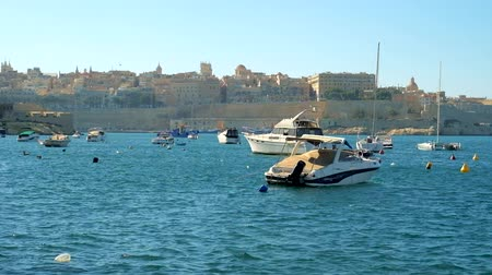 архипелаг : BIRGU, MALTA - JUNE 17, 2018: The view on the small boats in Kalkara marina and ramparts of Valletta from the seaside promenade of Birgu (Vittoriosa), on June 17 in Birgu.