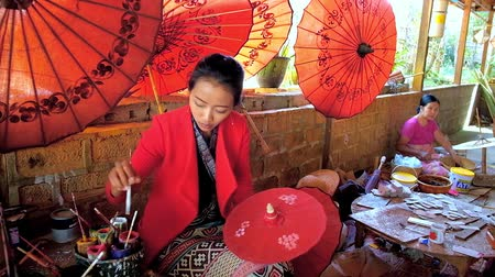 mianmar : PINDAYA, MYANMAR - FEBRUARY 19, 2018: The painter of Shan paper workshop decorates red handmade Burmese umbrella with traditional floral pattern, on February 19 in Pindaya.
