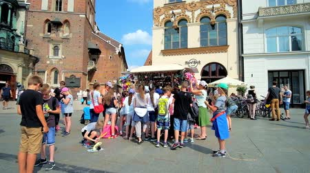 kamienice : KRAKOW, POLAND - JUNE 11, 2018: Kids make shopping at small toy stall in the Main Market Square, on June 11 in Krakow.