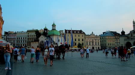 sukiennice : KRAKOW, POLAND - JUNE 11, 2018: The Main Market Square is popular place for the evening time spending, tourists enjoy carriage riding and make selfies with city landmarks, on June 11 in Krakow.