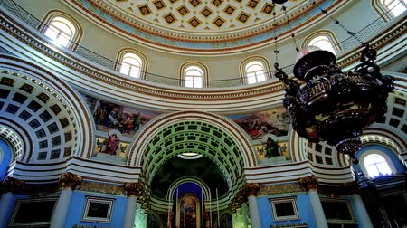 мальтийский : MOSTA, MALTA - JUNE 14, 2018: Interior of huge Basilica of the Assumption of Our Lady (Rotunda) with richly decorated arched niches, beautiful altar and impressive dome, on June 14 in Mosta.